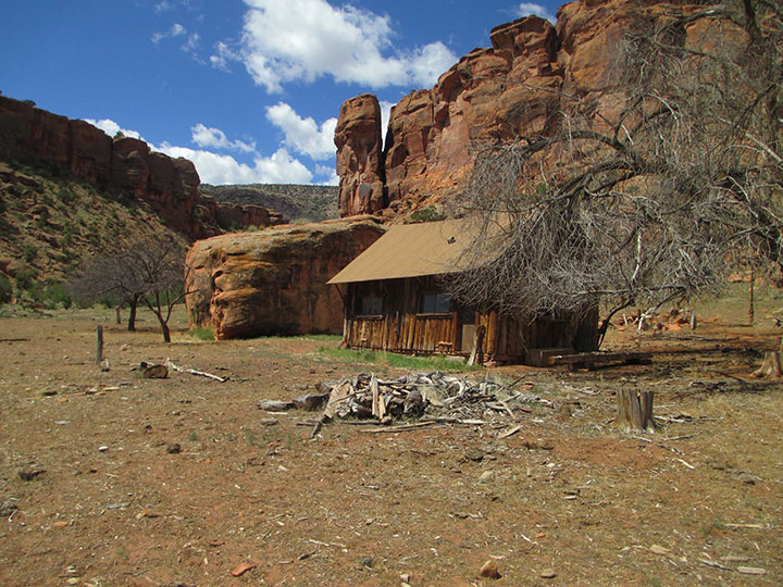 A historic wooden cabin sits below red cliffs.