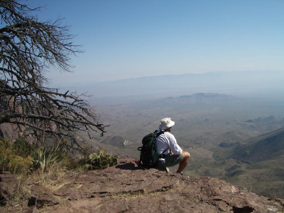 A lone hiker in a white shirt, sitting high on a rocky point, overlooking a massive desert valley far below.