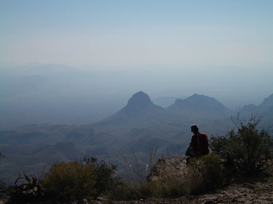 A lone hiker overlooking a desert valley far below, a lone rocky pinnacle stands high over its surroundings, engulfed in the surrounding blue haze.
