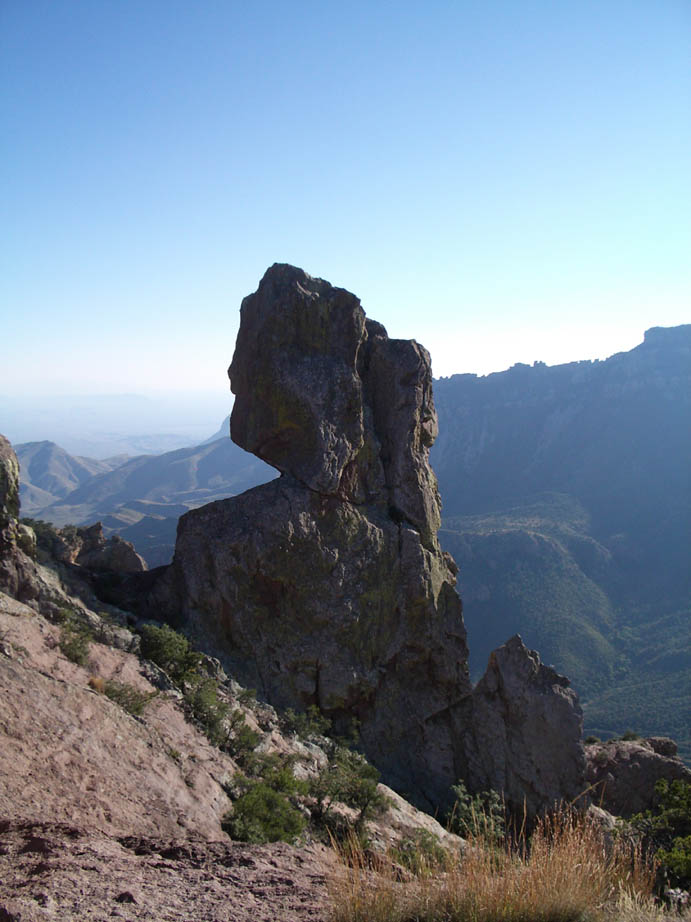 A massive rocky spire, standing high on the slope of a deep ravine, overlooking the valley below.