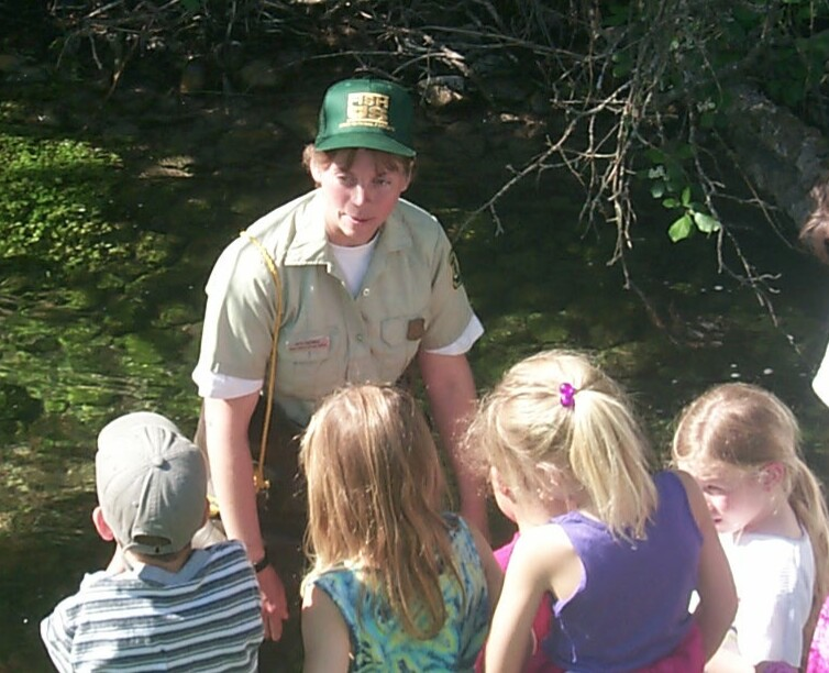An agency staff member standing near a small stream, speaking to a group of young children.
