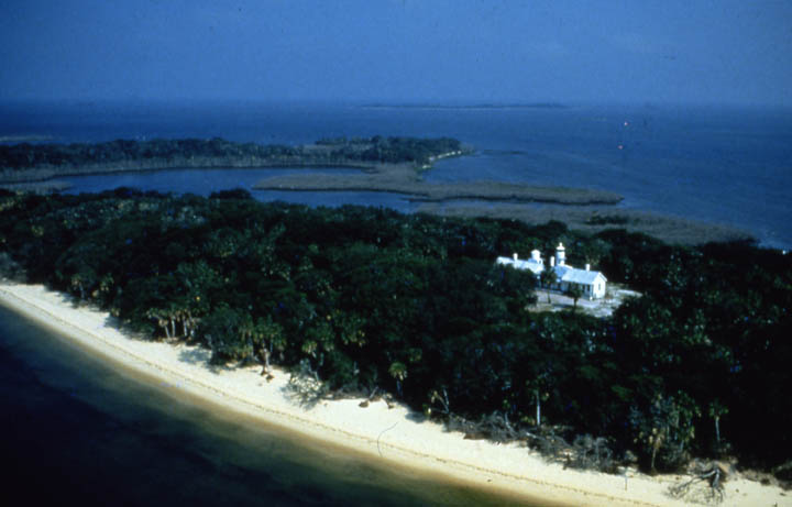 An aerial view of a small forested island with a white sand beach. A large structure stands in the center of the island, within a small clearing.