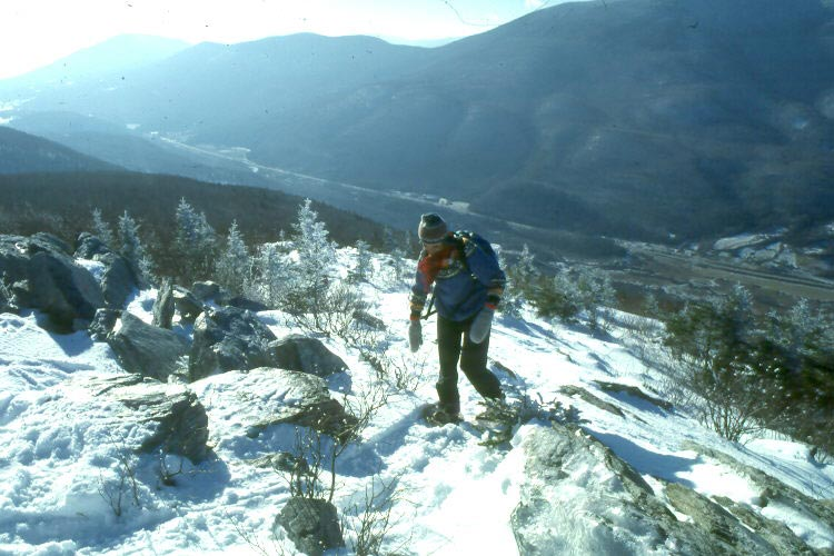 A lone hiker wearing snowshoes, trudging up a snowy slope with a large valley in the background.