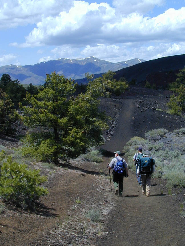 Two people carrying large backpacks, walking along a wide path of black sand. Large evergreen trees and sporadic brush dot the landscape, looking out to high mountains in the distance laced with snow.