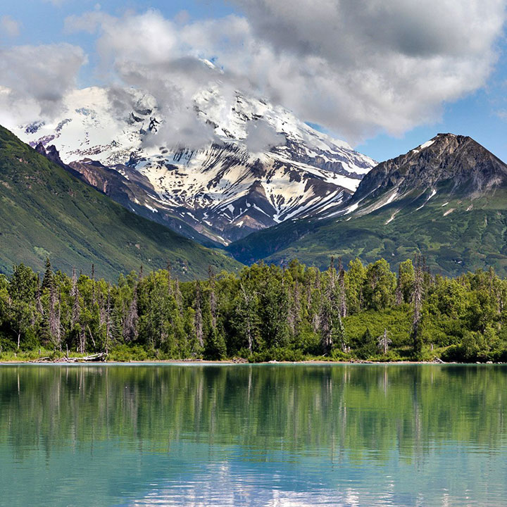 A snow-covered mountain sits in back of a lake