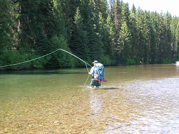 A man in a large blue backpack stands knee-deep in the green water of a river, fly fishing.