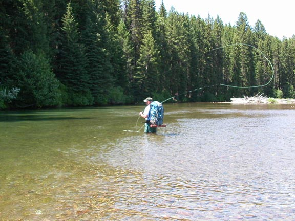A man with a large blue backpack fly fishing in the middle of a small river.