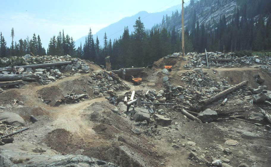A large disturbed gravel-pit area, surrounded by dense forest, and mountains in the background.