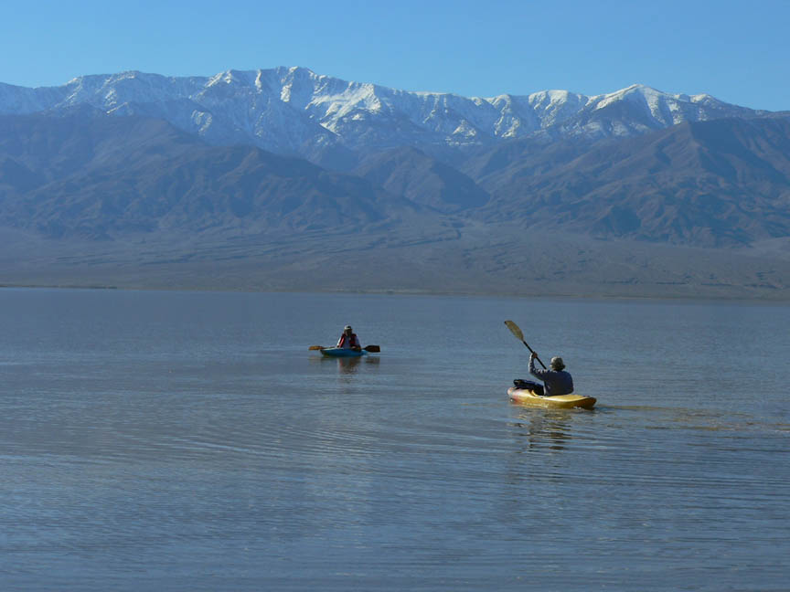 Two kayakers paddle across a large lake, a massive ridge rises across the lake, sweeping up to snow dusted peaks.