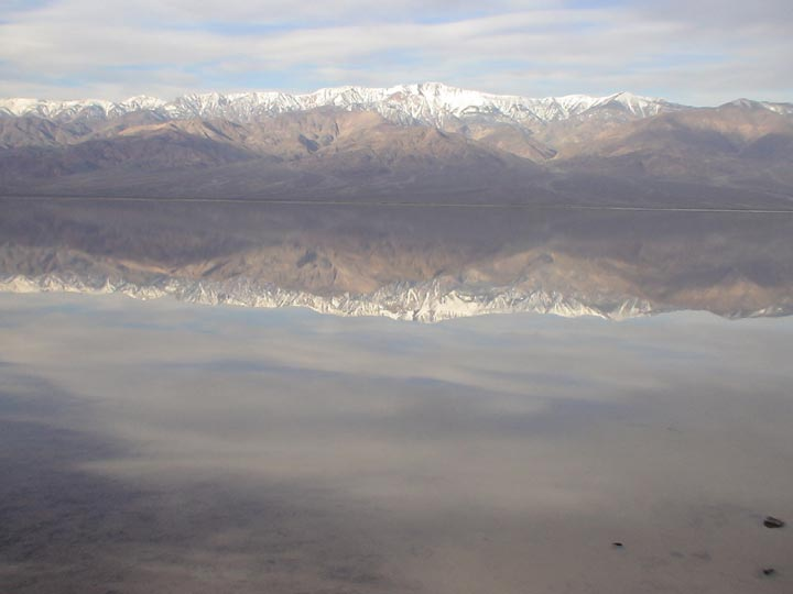 A still lake reflects a sky glazed over with clouds and the mountain range topped with snow.