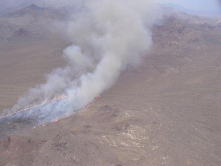 An aerial shot of a burn area where smoke billows out from the cinders.