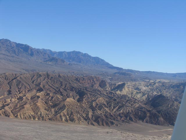 This photo is an aerial shot of the mountainous area of the Death Valley Wildness. The land rises up from a flat plane in rippling waves on a cloudless sunny day.