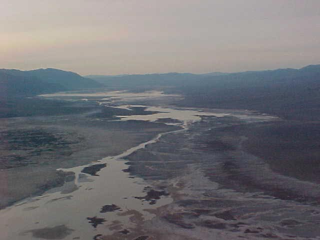 At dust, a stream in the Death Valley Wilderness meanders across the flatland.