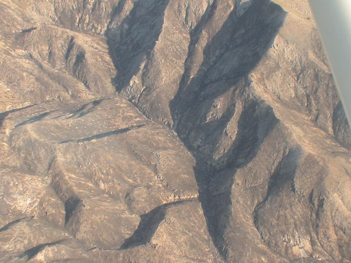 This is a close up of a mountain peak in the Death Valley Wilderness. The shot captures the rise of the rock edifices as they contrast to the base and cast shadows over the base.