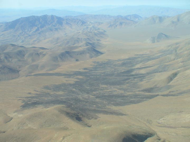This photo captures mountains and a long valley in the Death Valley Wilderness.