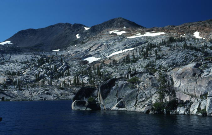 Viewing up from the shore of an alpine lake, to a bare rocky slope above, dotted with sparse evergreen trees and patches of snow.
