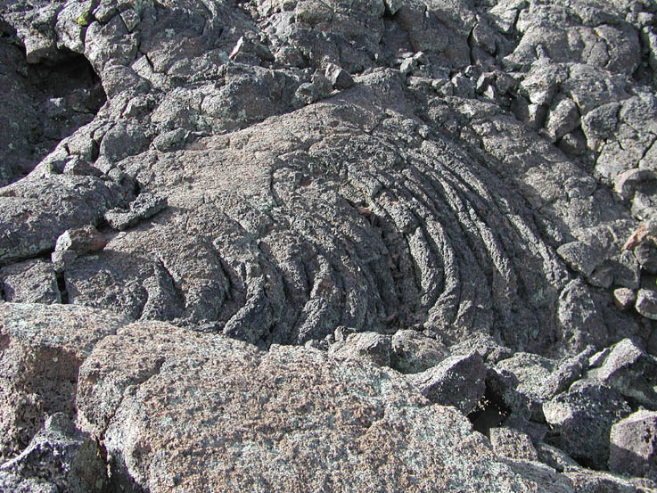 A close-up of textured gray lava rock, in a stretched fluid-like pattern.
