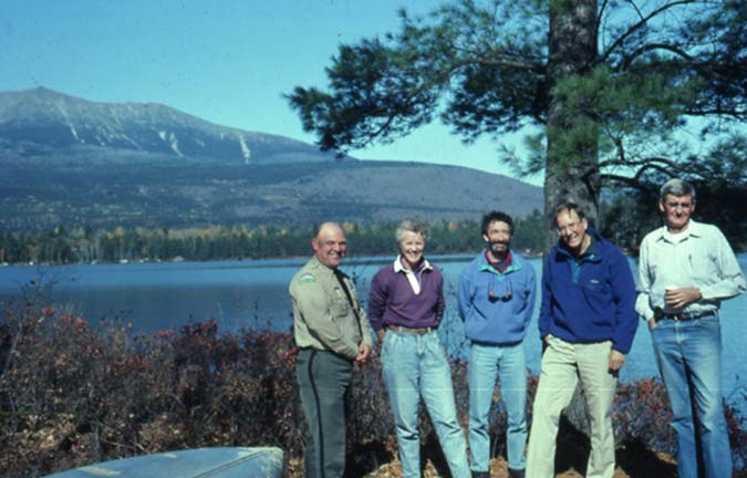 A group of five people standing at the base of a large tree, overlooking a lake in the background, and low mountains in the distance beyond.