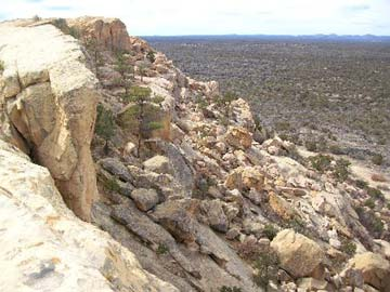 A rocky bluff with massive boulders piled below, along the edge of the valley floor stretching away into the desert landscape.