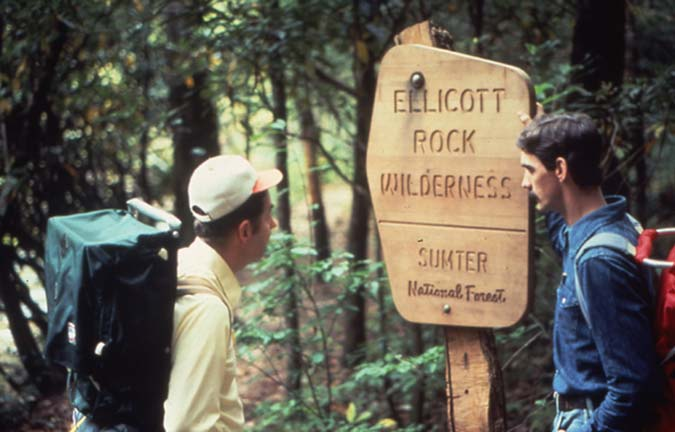 Two backpackers standing in the forest next to a brown wilderness boundary sign.