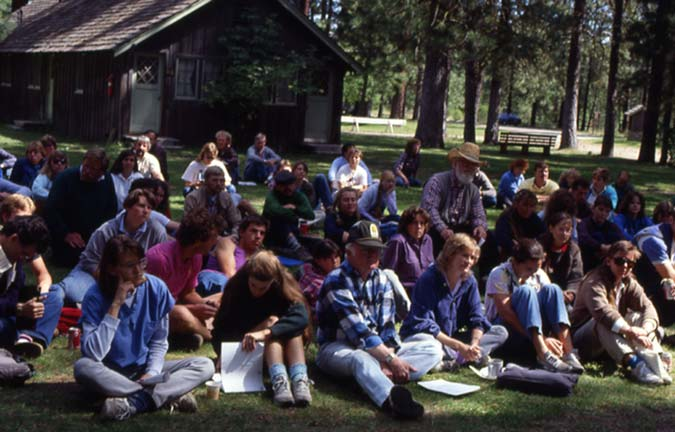 A large group of people sitting on a lawn, outside of a ranger station.