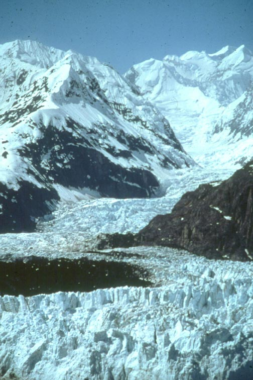 An immense river of jagged ice fills a valley, flowing down the back of a snowcapped peak.