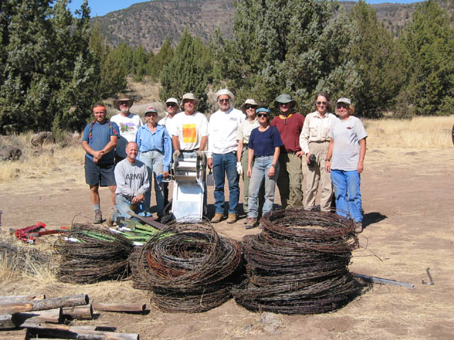 A group of workers standing in a small forest clearing, next to several large coils of rusty fence wire.