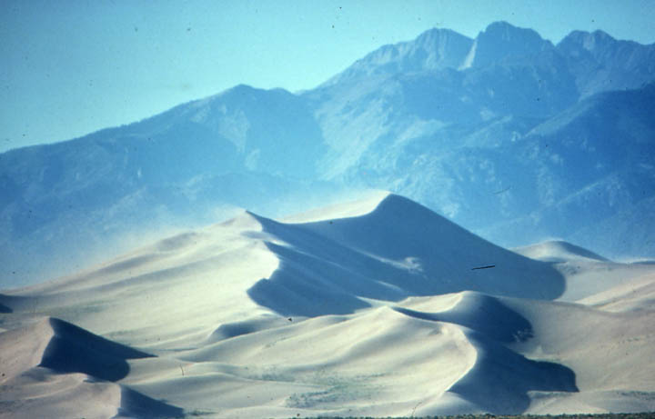 Massive white sand dunes whipped with wind, against harsh early morning light. Tall rugged mountains stand in the background, looming ominously over the landscape.