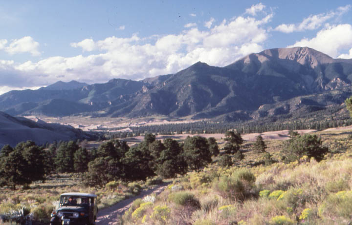 A jeep traveling up a narrow dirt road with an open valley stretching on behind, towards mountains in the distance.