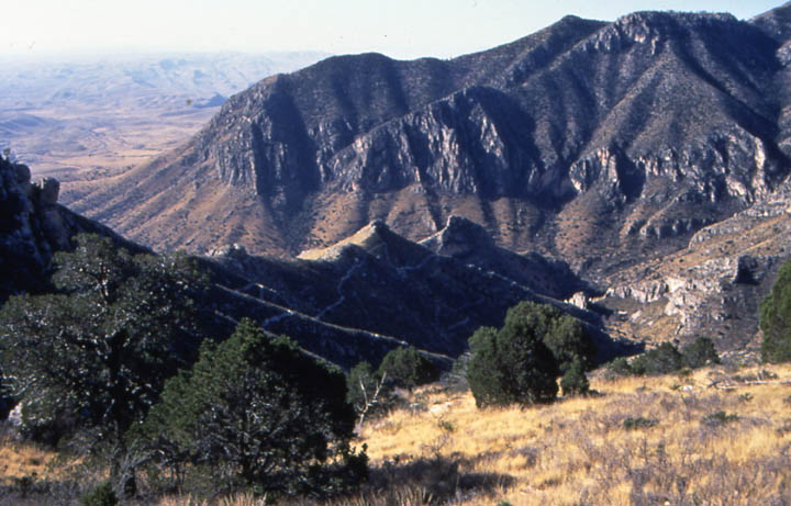 Looking down a mountain drainage filled with dry grass and sparse trees. Low mountains rise below, open slopes reaching to vertical cliffs above.