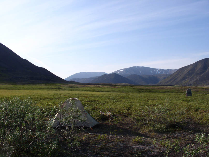 A small tent pitched on an open tundra valley, the grassy green stretching off into the distance towards low mountains.