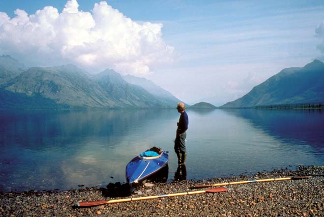 A man standing next to a kayak along the pebble shore of a placid lake, looking back over the still water to the mountains and puffy clouds in the distance.