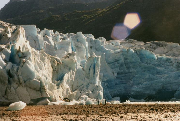 A close-up of a glacier terminus, two people dwarfed at the massive face of the fractured blue ice, rising high above the gravel flat.