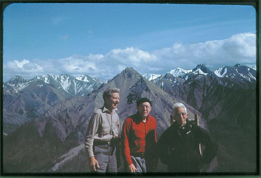 Three elderly men stand with a background of high snowcapped peaks in the background.