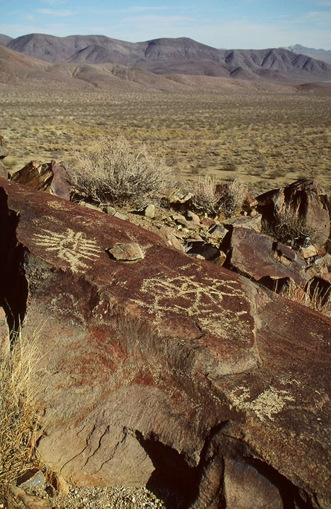Intricate petroglyphs etched on a large brown boulder in the foreground, an open desert valley stretching off beyond.