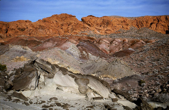 A desert wash in the foreground, of marbled red and gray sandstone backed by vivid orangey cliffs rising above.