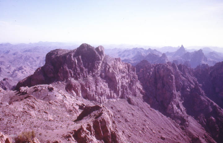 Looking down to a jagged desert mountain backed by countless jagged peaks, fading away into the hazy distance.