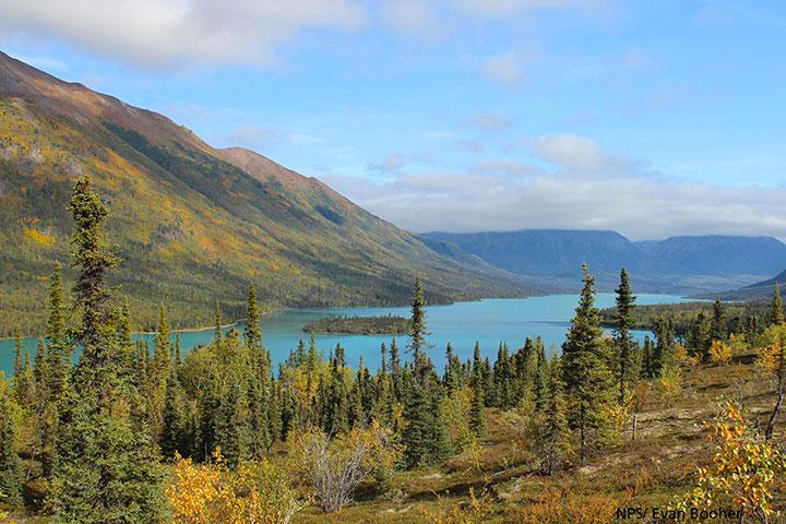 Fall foliage surrounds a large blue lake