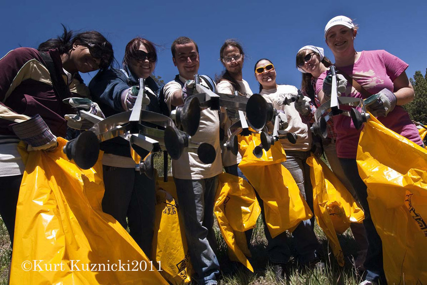 Wilderness volunteers hold up grabing tools and yellow bags.