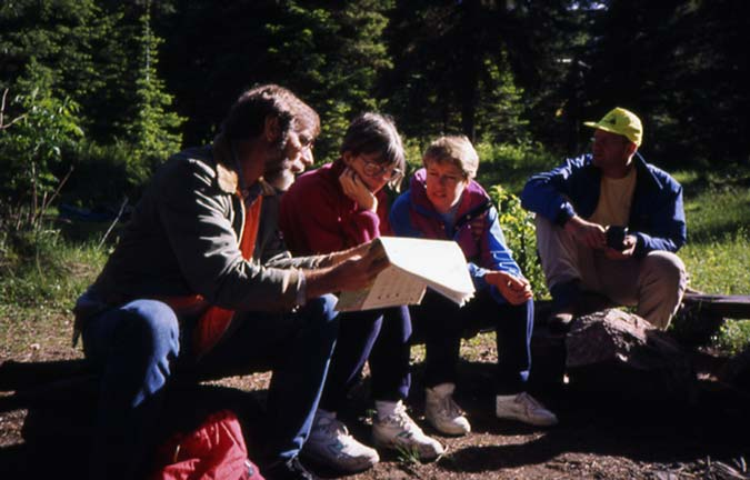 A group of four people sitting on a log, examining a map.