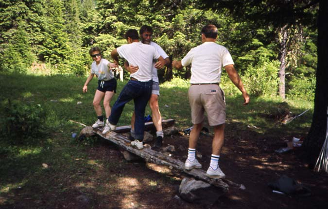 Four people standing on a log, conducting a team-building exercise.