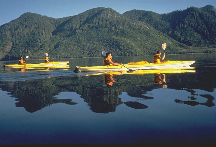 Three sea canoers paddle across a glassy lake.
