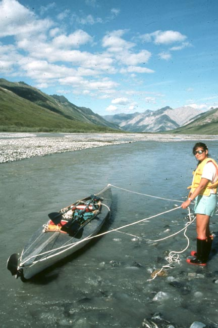 A woman in a yellow life vest, standing along the gray glacial waters of a small river, holding a gray kayak.