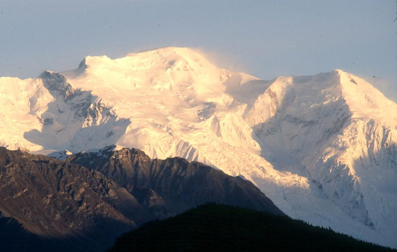 A massive ice capped peak drenched in golden morning light.