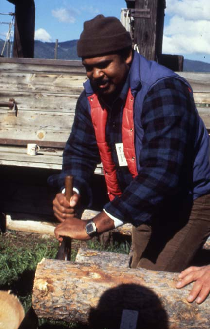 An African-American man, using a large hand saw to cut a log.