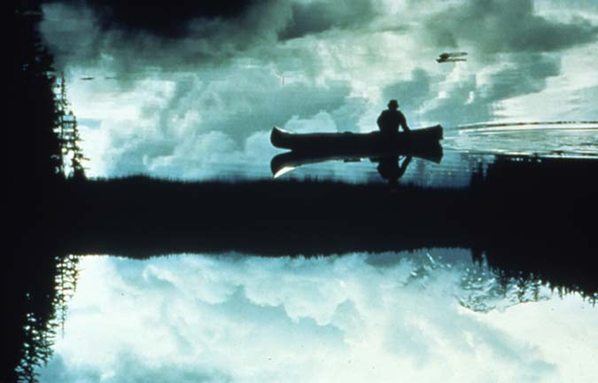 A painting of a lone canoeist along the edge of a placid lake, the cloudy sky reflecting off the mirror surface of the water.