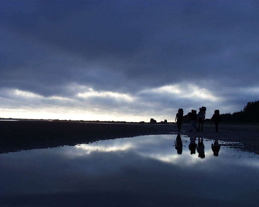 A moody image of a small group of backpackers silhouetted against an evening sky, their reflection from a large puddle in the foreground mirroring the blue cloudy sky above.