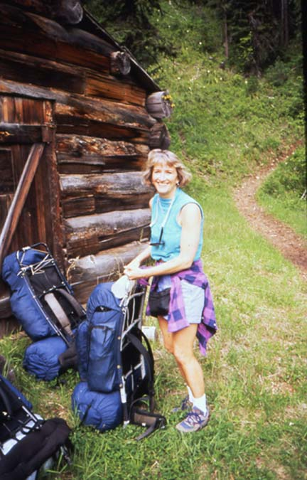 A woman in a light blue shirt, loading a backpack next to an old log cabin, along the edge of the forest.