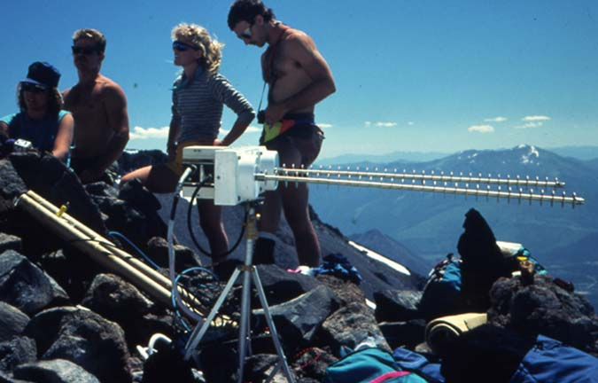 A group of researchers operates a radio tracking device on a mountaintop.