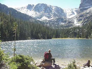 A lone backpacker sits on a large rock along the shoreline of a sparkling alpine lake, looking up to high rocky peaks rising from the far shore.